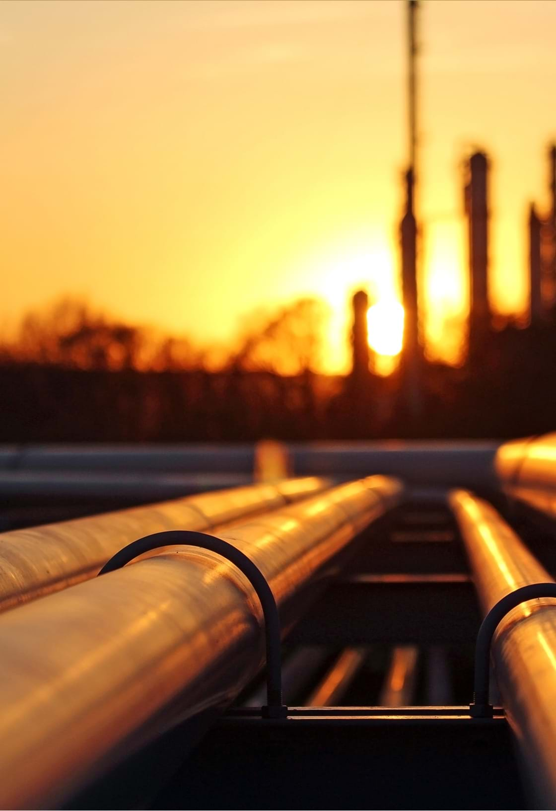 image of a power plant and pipelines, sunset